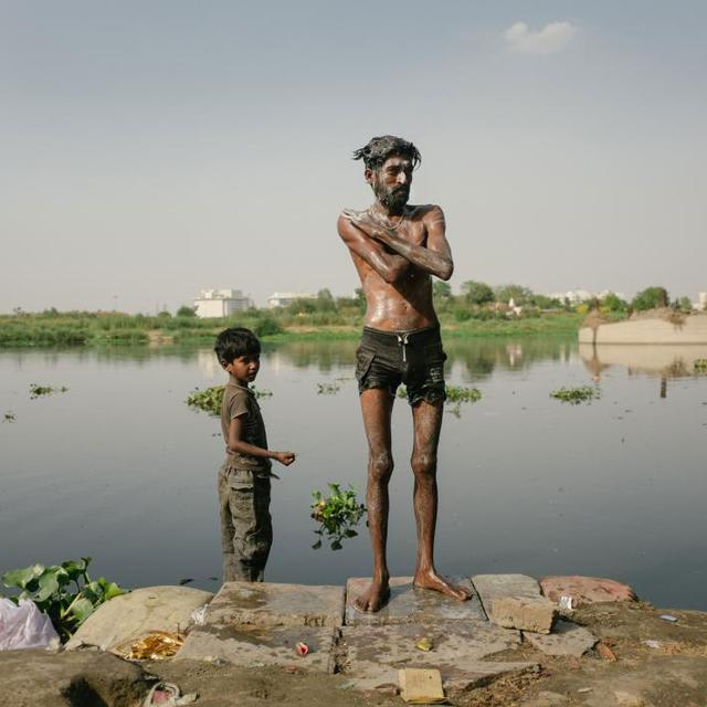 Hai cha con đang tắm trên sông Yamuna. Vì quá ô nhiễm nên chính quyền đã cấm người dân cho gia súc tắm dưới sông.