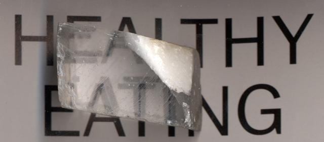 Ánh sáng đi qua tinh thể canxít tạo ra hai ảnh của chữ viết nằm bên dưới, tương ứng với tia thường và tia khác thường.