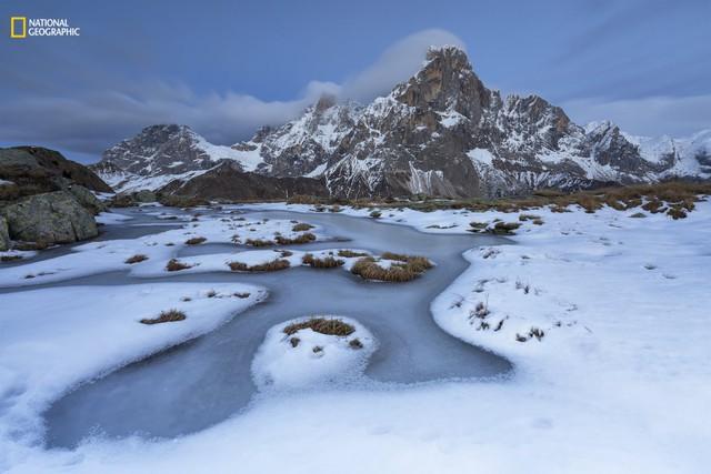 Ngày đầu tiên cái lạnh kéo đến đã làm đóng băng mặt nước, trận mưa tuyết đầu tiên mang một vẻ đẹp tinh tế. Được chụp trong điều kiện áp suất thấp, gió tây nam đẩy những đám mây tới những đỉnh núi thẳng đứng của Pale di San Martino.