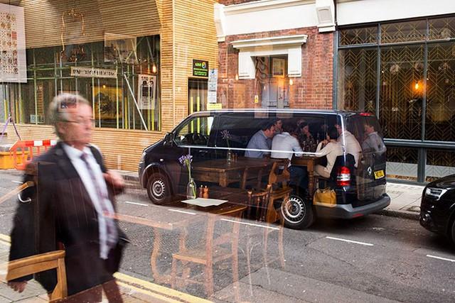 Không gian nhà hàng bên trong phản chiếu qua tấm kính, khiến các vị khách như đang dùng bữa ngoài ô tô