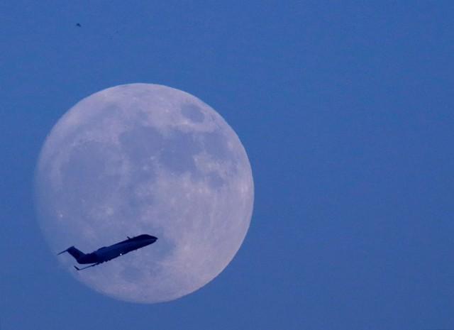 Máy bay bay ngang qua bầu trời Kathmandu ở Nepal, với hậu cảnh mặt trăng. Ảnh: Reuters.