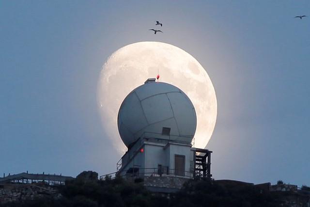 Trăng rằm dần xuất hiện trên nóc một tháp quan sát tại vùng lãnh thổ Gibraltar của Anh. Ảnh: Reuters.