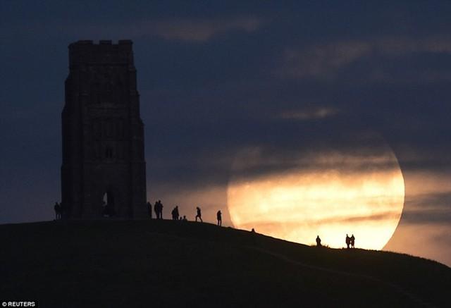Người dân thị trấn Glastonbury quan sát mặt trăng dần mọc trong đêm 13/11. Để quan sát tốt nhất, người xem nên rời khỏi thành phố vì ánh đèn đô thị và các đám mây có thể làm lu mờ mặt trăng, khiến nó chỉ trông giống như trăng tròn bình thường.Ảnh: Reuters.