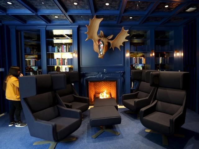 Tông màu xanh nhẹ nhàng kết hợp với sự ấm cúng bên lò sưởi thư viện