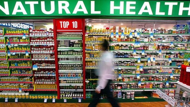 Một người đàn ông đi ngang qua gian hàng bày bán đủ loại thực phẩm chức năng