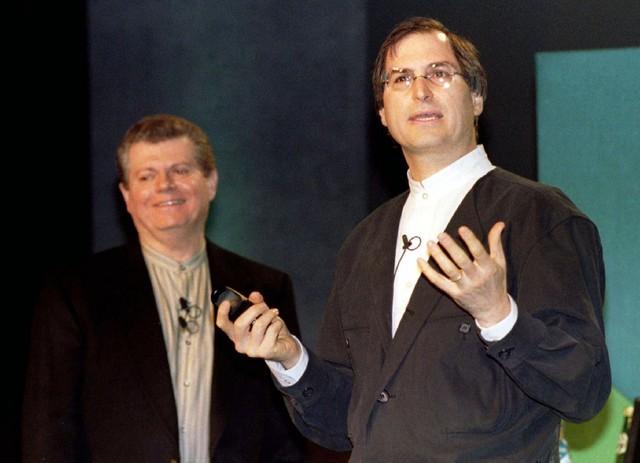 Vào cuối năm 1996, Apple thông báo dự định mang nhà sáng lập Steve Jobs trở lại công ty 11 năm sau khi ông rời đi bằng cách thâu tóm startup NeXT của ông với giá 429 triệu USD - vừa kịp thời gian để Jobs đứng cùng sân khấu với CEO Apple vào thời điểm đó là Gil Amelio trong sự kiện Macworld Expo vào tháng 1 năm 1997, một hội nghị dành cho những người yêu thích Mac.