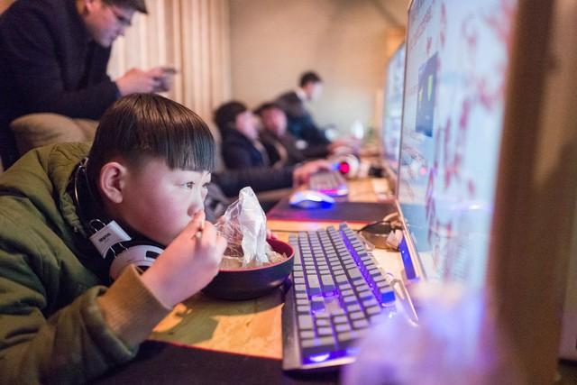 """Một """"game thủ"""" nhí ăn tối ngay trên bàn, mắt vẫn dán chặt vào màn hình máy tính"""