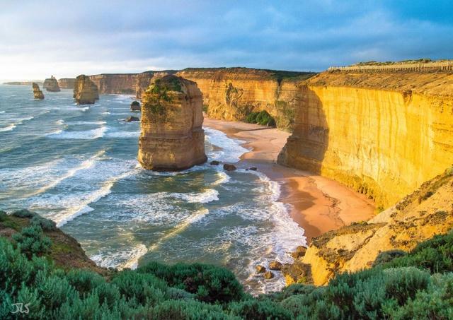 """Twelve Apostles – hay còn có tên gọi là """"12 tông đồ"""" thuộc công viên quốc gia Port Campbell Victoria là những cột đá vôi khổng lồ, cao tới 45m, đứng chơ vơ giữa biển nước mênh mông. Đây là di tích còn sót lại của sự xói mòn nước biển lên các dãy núi đá vôi có từ hàng chục triệu năm trước, để lại những hình thù kì thú."""