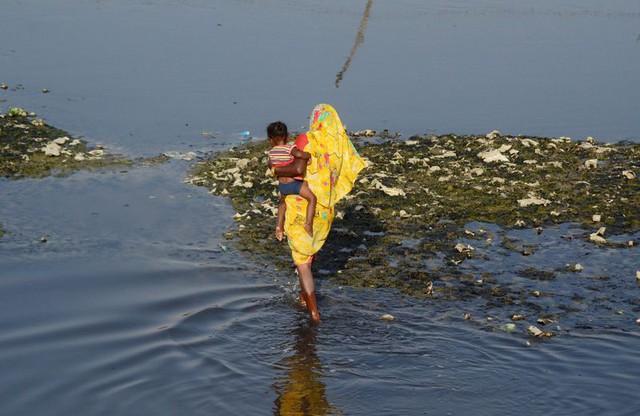 Một người phụ nữ Ấn Độ bồng con, đi chân trần trên một đoạn sông ô nhiễm
