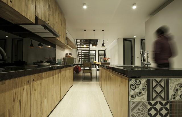 Khu vực bếp được thiết kế cùng ngôn ngữ gọn gàng và hiện đại. Gỗ và gạch bông được sử dụng như một sự kết hợp thật hài hòa.