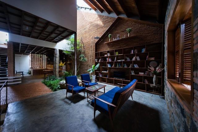 Phòng khách mộc mạc với hệ tủ sách và thông tầng lấy sáng. Không gian tầng 1 hoàn toàn không có các loại vách ngăn chia, sự ngăn cách được hình thành ước lệ thông qua sự khác nhau của vật liệu sàn và đèn trang trí