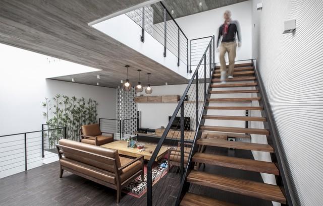 Phòng khách tràn ngập ánh sáng tự nhiên vào ban ngày. Thang không cổ bậc giúp không gian được thanh thoát, giảm bớt sự nặng nề của vật liệu bê tông không trát đem lại.