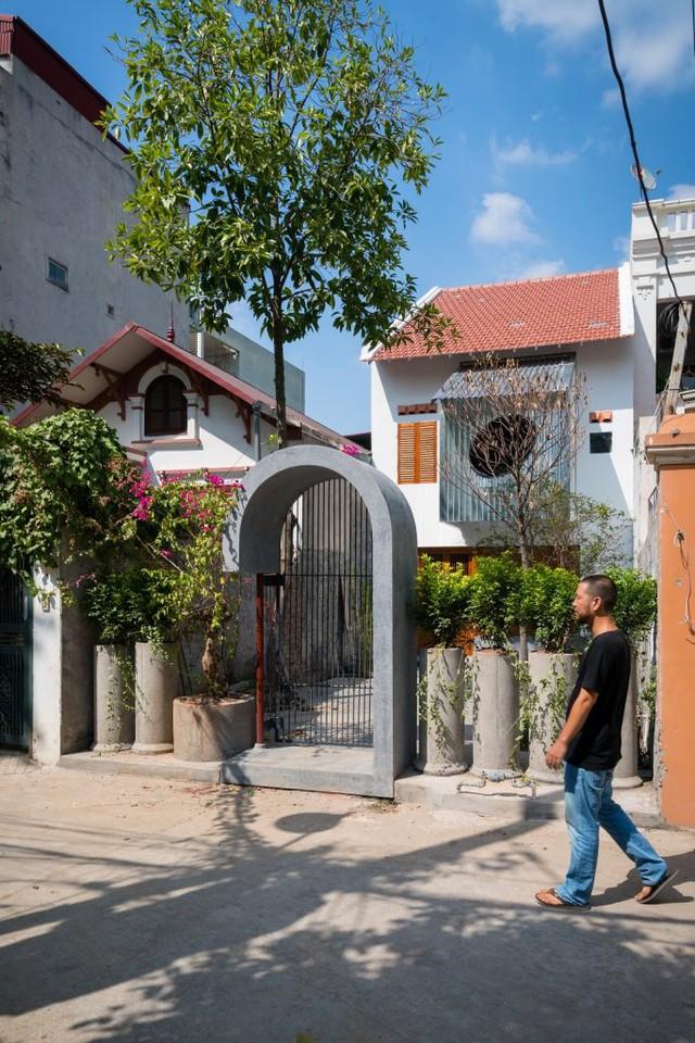 Ngôi nhà chỉ được ngăn cách một cách ước lệ bởi cổng vòm, cùng hàng cây được trồng trong những ống bê tông cũ. Như một sự gửi gắm rằng, ngôi nhà luôn chào đón những vị khách thân thiện xung quanh. Tất nhiên, vấn đề an ninh vẫn sẽ được đảm bảo.