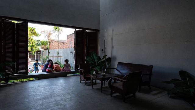 """Mọi người trong gia đình ngồi quây quần bên """"con ngạch"""". 2 khe hở nhỏ được thiết kế để giúp gió được lưu thông liên tục trong ngôi nhà, ngay cả khi cửa chính đã được đóng kín"""