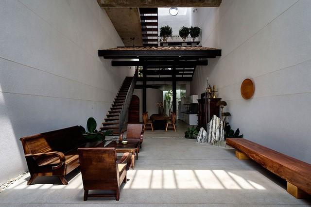 Phòng khách được thiết kế với chiều cao thông thủy lớn, tuy nhiên, đồ nội thất và mái nhà cũ giúp không gian có điểm nhấn và trở nên ấm áp hơn