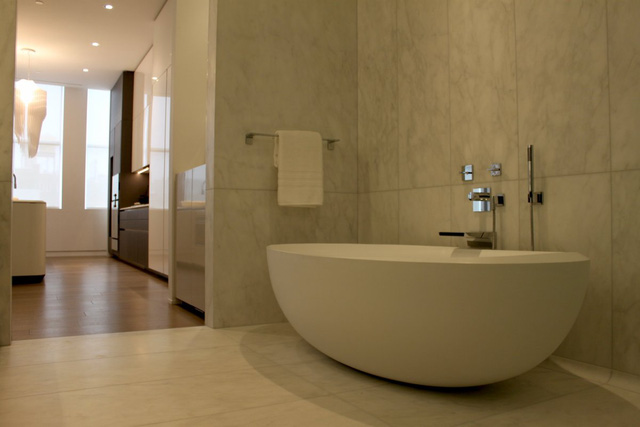 Phòng tắm có sàn làm bằng đá cẩm thạch, vòi hoa sen và bồn tắm dài 6 foot.