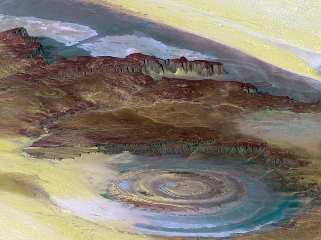 """Richat Structure ở Mauritania, còn được biết đến với cái tên """"con mắt của Châu Phi"""" tại sa mạc Sahara là một kết cấu địa chất hình elip nổi lên giữa sa mạc Sahara ở trung tâm phía Tây nước Mauritania, gần khu vực Ouadane. Công trình tự nhiên này là kết quả của sự xói mòn đất từ cuối thời kỳ Nguyên sinh cho đến giữa thời kỳ Sa thạch Ordovicia."""