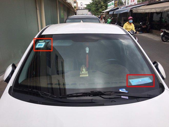 Một xe GrabCar gắn phù hiệu Xe hợp đồng và tem GrabCar ở kính xe. Ảnh: Grab