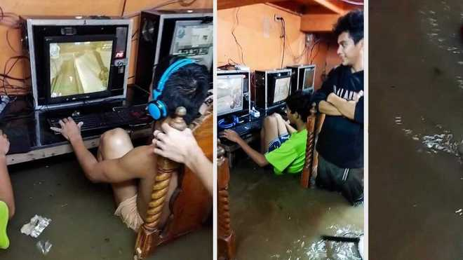 Game thủ nhí phớt lờ nguy cơ bị điện giật, chìm đắm trong game khi quán net ngập nước lũ - Ảnh 1.