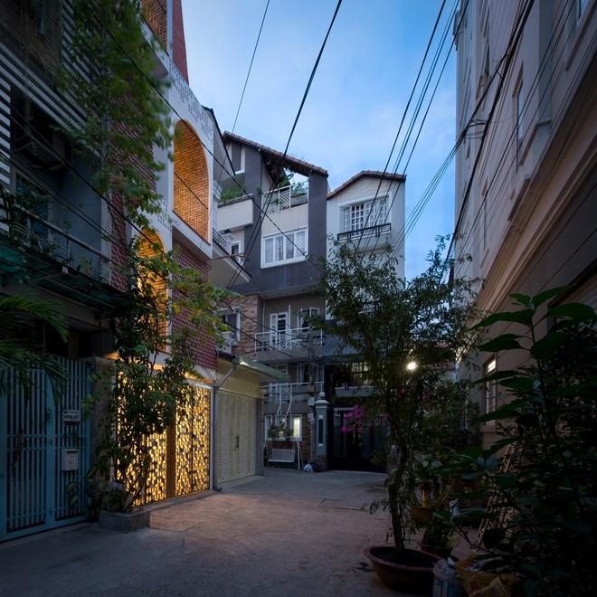 Ngôi nhà nằm trong một ngõ nhỏ ở Tp Hồ Chí Minh. Xung quanh đều là nhà ống cao tầng, mặt trước là đường bê tông rộng 3,5m.