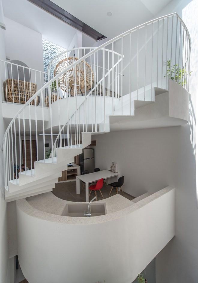 Phần cầu thang ở cuối nhà được thiết kế với hình thức cong. Một mặt do diện tích ngôi nhà hạn chế, mặt khác giúp không gian ngôi nhà nhẹ nhàng và mềm mại hơn.