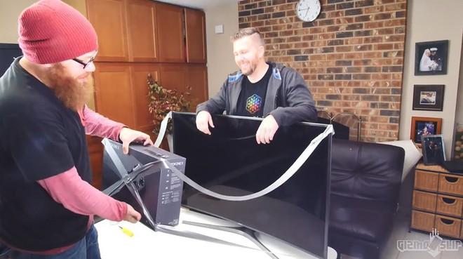 Hai người thực hiện nối chiếc TV với hộp Xbox One bằng một đoạn dây vải