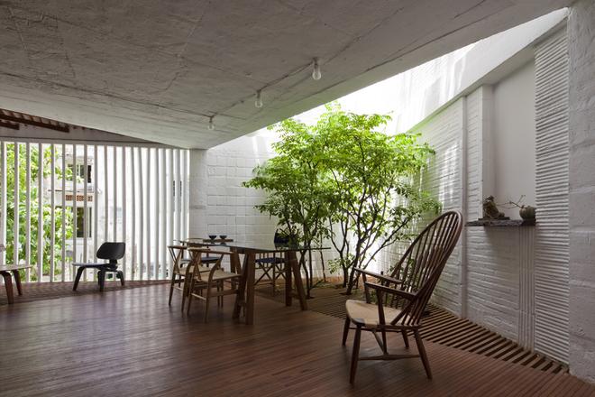 Một góc không gian tiếp khách của công trình. Các miếng sàn lam gỗ giúp ánh sáng có thể len lỏi xuyên xuống các tầng không gian bên dưới, tạo điều kiện cho cây xanh có thể phát triển.