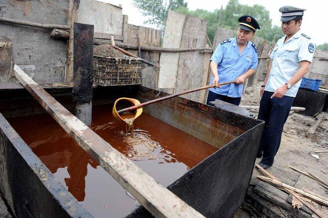 Cảnh sát đang kiểm tra một cơ sở chế biến dầu ăn bất hợp pháp, trong một đợt truy quét vào tháng Tám 2010.