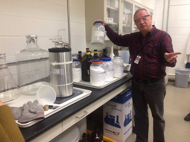 Một nhà khoa học đang cầm chiếc bình rỗng vốn được dùng để đựng nguyên liệu dùng cho các thí nghiệm của mình.