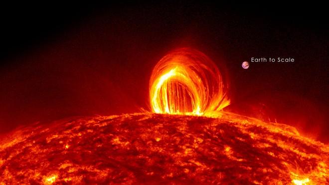 Vỏng lửa trên bề mặt Mặt Trời, quả bóng tròn nhỏ bên cạnh kia chính là Trái Đất của chúng ta.