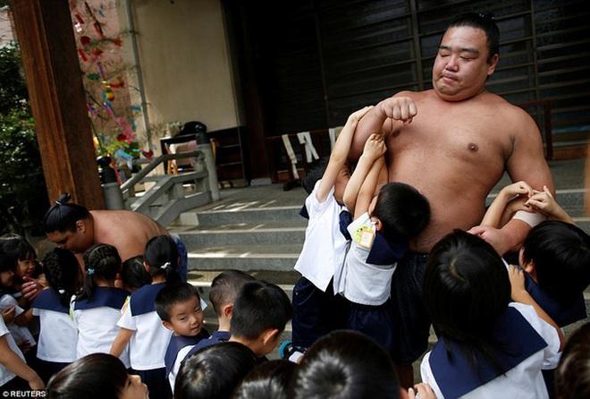 Võ sĩ sumo Kainoryu chơi với các em nhỏ tại ngôi đền Ganjoji Yakushido.