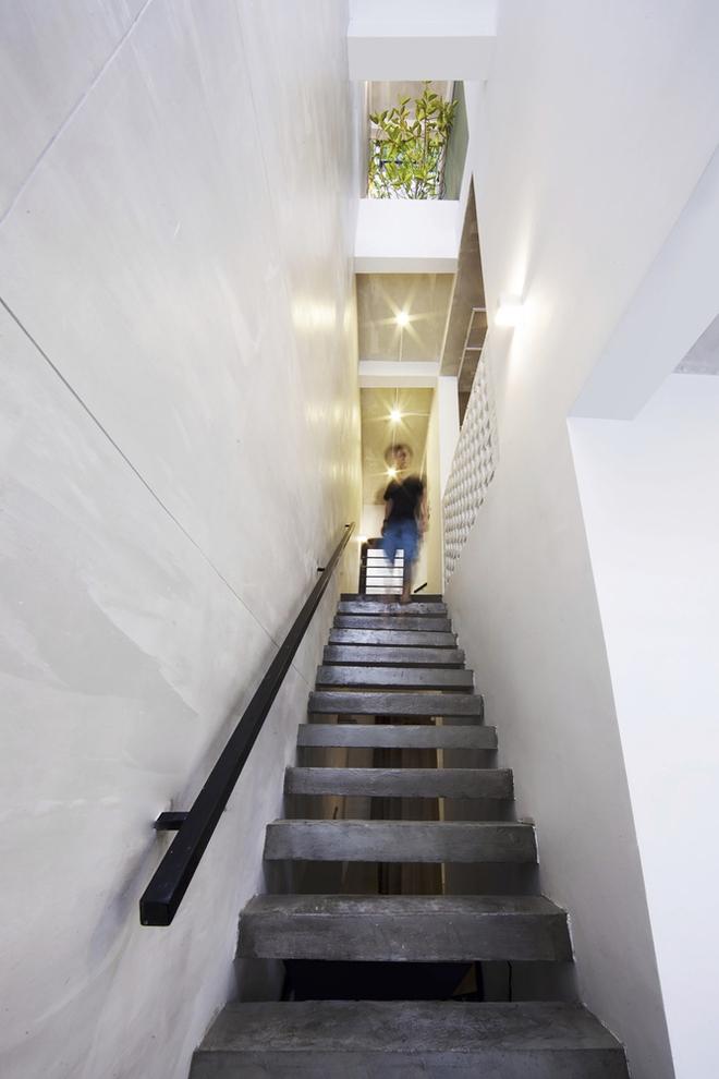 Cầu thang bê tông đúc tầng hai và ba được chuyển hướng từ bên trái ngôi nhà sang mặt sau