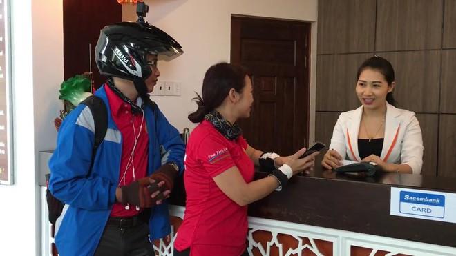 Anh Thịnh và chị Huyền đang chia sẻ với một nhân viên khách sạn về sự tiện dụng, thuận lợi của Samsung Pay