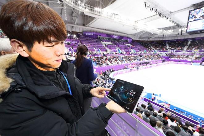 Một khán giả đang theo dõi một màn thi đấu tốc độ thông qua một thiết bị ứng dụng công nghệ Time Slice, cho phép quan sát mọi hình ảnh ở góc quay 180 độ nhờ sự hỗ trợ của 100 máy quay lắp đặt xung quanh sân Gangneung Ice Arena