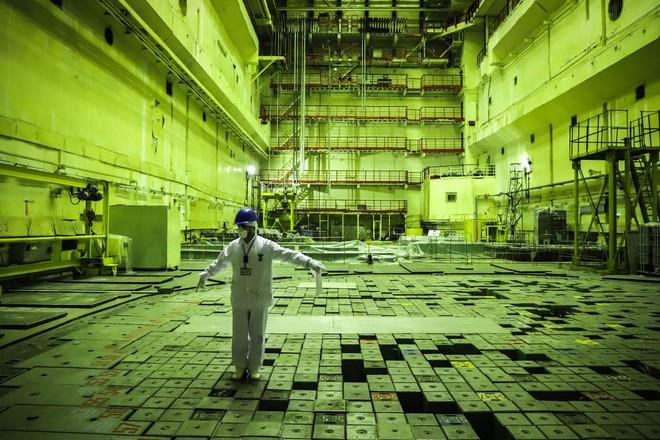 Một hướng dẫn viên của nhà máy đón mọi người vào trong sảnh lò phản ứng.
