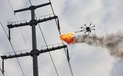Trung Quốc dùng drone phun lửa để dọn rác mắc trên đường dây điện cao thế